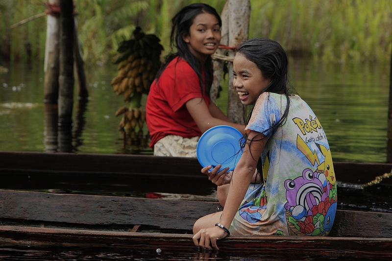 Two girls below a sit in traditional hand crafted canoes under their home raised on stilts by the river bank. Fishing families spend part of their time in the depths of the rainforest to catch fish they sell at local markets for income.