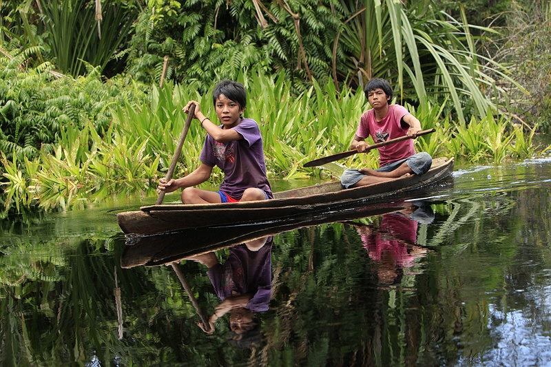 Two young boys in a traditional locally hand crafted canoe on a water way close to the Serkap River.