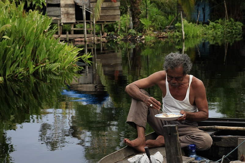 Pak Dani Jambang eating rice for breakfast outside his fishing hut in threatened peatland rainforest. Here his family have made a living for over half a century, but now their livelihood is in danger as the logging companies move in.