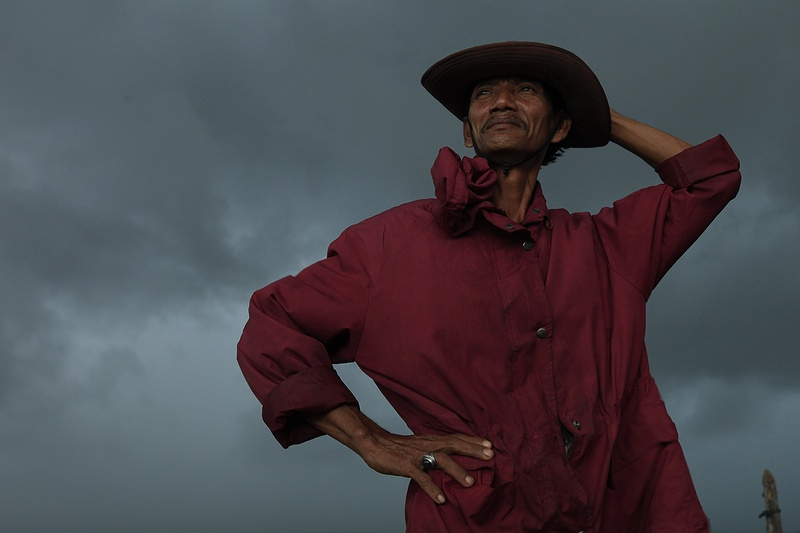 A 'pompong' boat driver from the village of Teluk Meranti looks out over the Serkap River at an approaching storm.