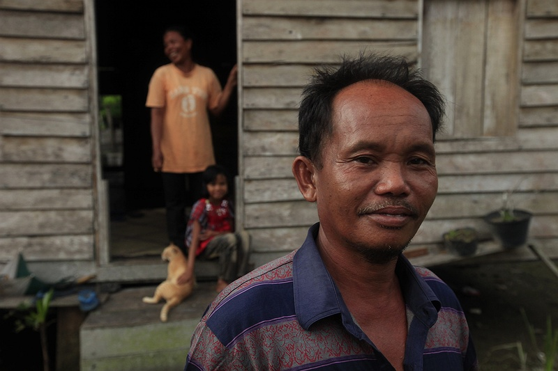 Mohammed Yusuf in front of his home in Teluk Meranti with his daughter, wife and cat.