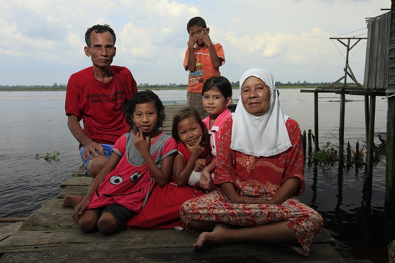 Mr Junus and his family sit on the jetty outside their home by the Serkap River. Mr Junus volunteers for Greenpeace who have set up a camp locally to try to stop the deforestation. His family are against the companies claiming their land and are dependent on the forest for their livelihood.