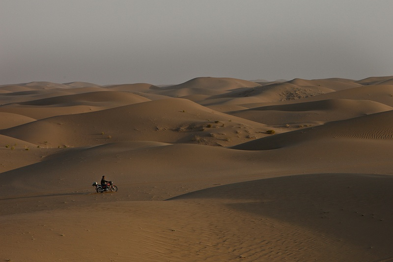 A biker rides through the dunes on the outskirts of the Badain Jaran desert north of Wuwei, China. Every year the desert expands several metres as deadly sandstorms from the north become a more frequent phenomenon. When an area has been taken over by the desert it is almost impossible to reclaim it back.