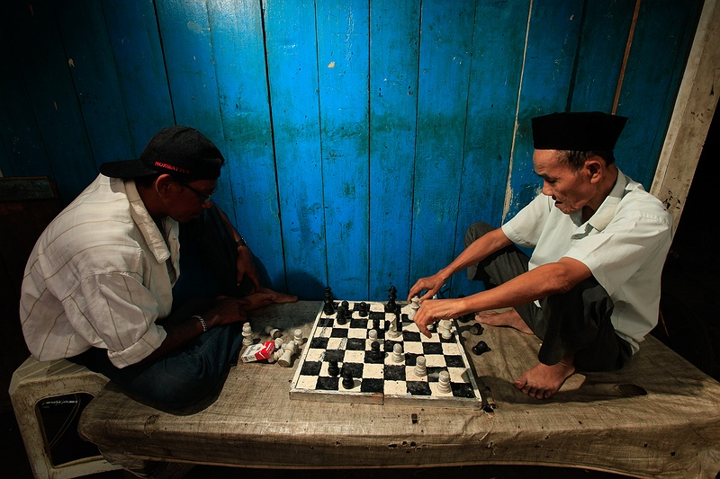 Two men play chess in the harbour slums by Jakarta's sea front. With a population of nearly ten million people the estimated sea level rise by the end the century will have a dramatic effect on Jakarta's population. One of the poorest areas of the huge city are the slums by the sea. A predicted rise in sea level of 5 centimetres by 2025 will be magnified by that the city itself is sinking with an average of 5 centimetres per year.