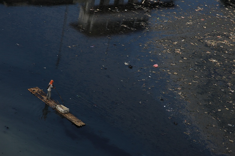 A man collects valuable garbage from one of Jakarta's rancid canals. Designed to cope with  floods, Dutch colonists built an intricate web of canals that should divert excess water towards the sea. Poor maintenance and increasing rubbish leave these important water ways blocked.