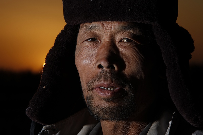 Cotton farmer Mr Chenang lives with his family in the Minqin district of Gansu province. It is a thin oasis of land fenced in by the advancing Tengri and Badrain Jaran deserts. The desertification is relentless, several metres of farmland disappear every year. Without breaking from his cotton picking for 3 Yuan a kilo, Mr Chenang remarks,
