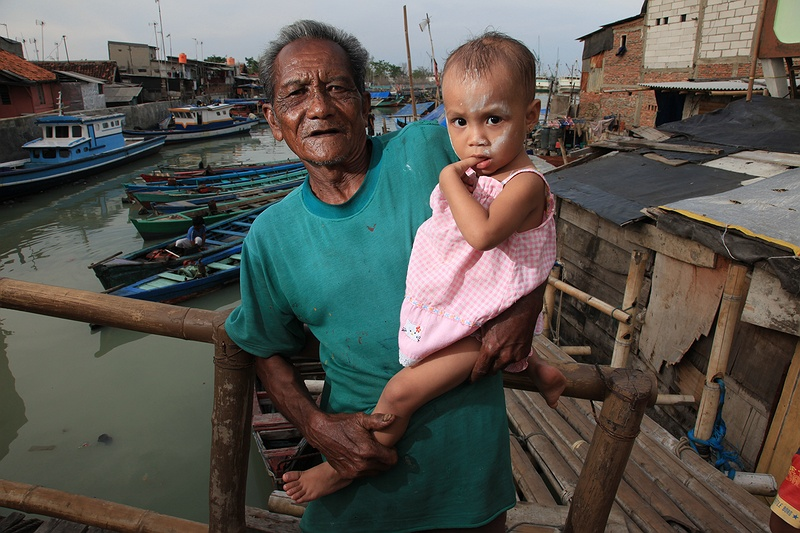 Life in the slum. An old man and his grand daughter stand on one of the bridges over a sewage canal joining the slum together. Some of the poorest and most densely populated areas of the city are around the north where extensive networks of slums house economic migrants from all over the country. They come to settle in the capital in the hope of a better quality of life and to find employment. It is these communities that will be hit the hardest by climate change as their homes are mostly built into the sea.