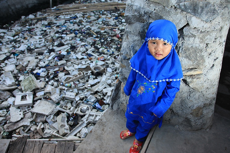 A young girl outside her family's home in one of the seafront slums of Jakarta. The UN Human Settlements Program estimates that 26 percent of Indonesia's urban population live in slums. Greater Jakarta housing some 5 million alone.