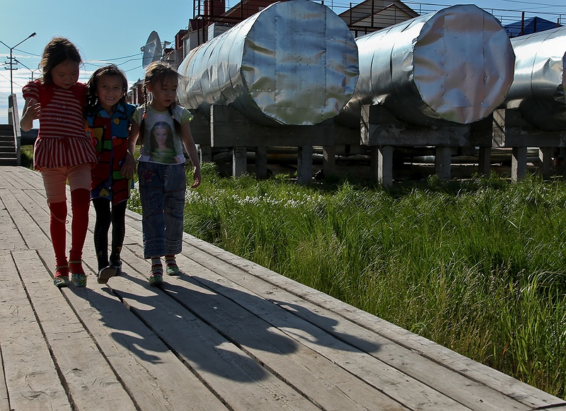Three friends walking on a boardwalk by some over ground tanks. Water, fuel and gas tanks are all above ground in Yar-Sale as the town is built on [tag permafrost permafrost].