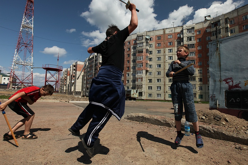 Three boys sword fighting with sticks outside their home in Neryungri. The city was built and boomed in the 1970s when coal was first discovered here. The pale pink decrepit apartment blocks are a reminder of the city's functional purpose. Despite all the money that has been extracted from the ground, not much money goes back into the community. Neryungri's trade routes will be affected as roads and railway lines built on previously considered stable ground [tag permafrost Permafrost], begins to thaw.