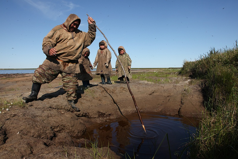 Anatoliy Hoodi pokes a thermokarst lake with a stick to show us the methane gas that bubbles up from decomposing organic residues. He is also standing on what used to be a large lake which completely subsided and drained in what Anatoliy describes as an
