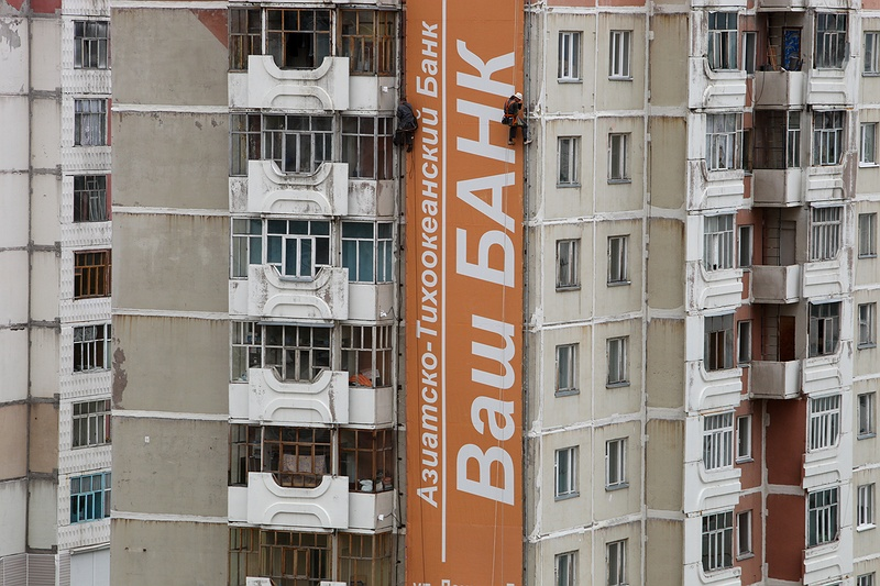 Climbers set up a bank commercial for loans on one of the apartment blocks in the coal mining city of Neryungri. Despite the wealth of the fossil fuel industry this town remains very bleak and poor.