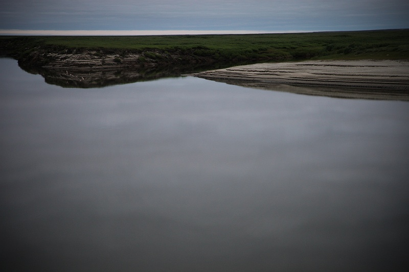 The overcast sky is reflected in the Yuribey river. Yamal is home to one of the world's biggest known gas reserves and the peninsula is now being exploited by Gazprom, threatening the Nenets' traditional way of life. Gazprom are already battling to create secure pipelines that will have to adjust to the changing ground underneath as the landscape thaws.