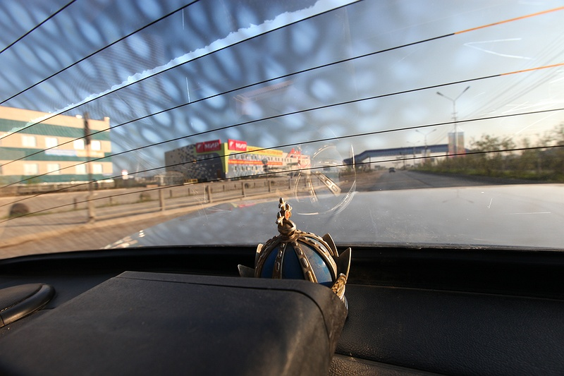 Bumping through the subsiding and collapsed roads of Yakutsk in a Russian Orthodox Christian Lada Taxi. With 30 percent of the city's buildings collapsing and industrial infrastructure crumbling, the cost of repairs is everyone's concern.