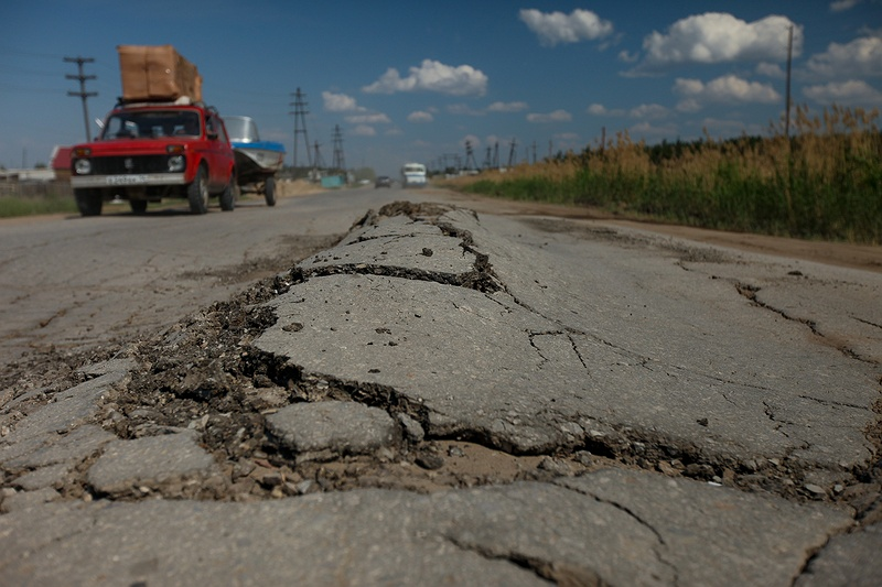Buckled tarmac on a subsiding road outside Yakutsk, the coldest and largest city built on permafrost in the world. Yakutsk has some of the greatest seasonal temperature differences dropping to -50°C in the winter with summer peaks of over +30°C.