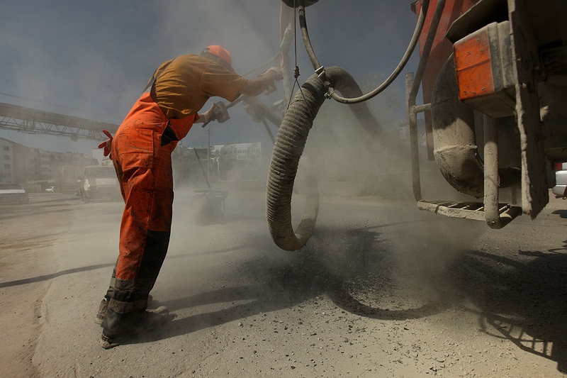 A worker fills tarmac into cracks caused by unstable ground under a road in Yakutsk. If the permafrost thawing continues this area could face huge problems with landslides and increased infrastructure damage.
