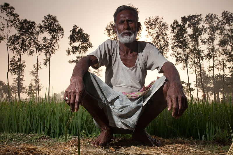 By dawn, the fields are alive with activity. In May the days are becoming agonisingly hotter and the mid day sunshine is unbearable.  Rice farmer Ismael Khan is tending to his paddy field before the scorchingly hot mid day sun.  Without our translator, we managed to converse with our Bengali and were welcomed to his home for tea.