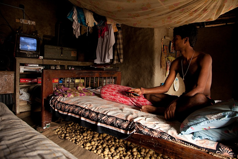 Son of Shasanka Das watches Street Fighter on TV in his bedroom. The Das family have a successful betel leaf plantation and are one of the more affluent families on Sagar Island.  The families potato crop that will keep them fed throughout the year is stored under his bed.