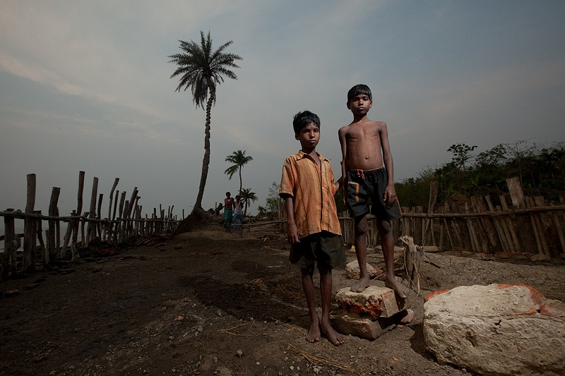 Two boys stand on the remains of the previous flood defences smashed by Cyclone Aila. The cyclone destroyed the walls built to defend against storms and tidal surges in just a few hours. Efforts to restore them are under way, but it will take time to complete and the monsoon season is imminent.