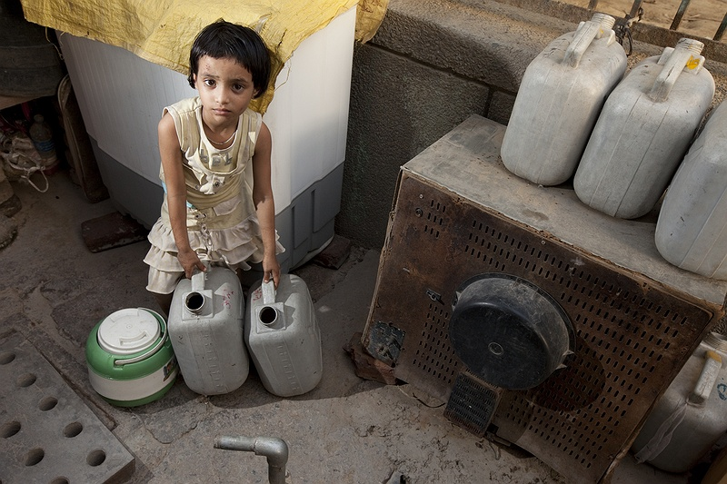 A little girl fills water cans in Shiva Nand cluster in Delhi. All drinking water is transported here by special water trucks. Based on current trends, over the next 20 years humans will use 40 percent more water than they do now according to United nations environmental program.