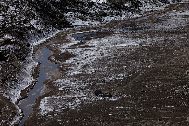 A stream of melt-water by the Tapovan meadow. The stream will eventually flow down into the Ganges. This barren area 4,000 metres above sea level is a seasonal home to various sadhus living in caves engaged in spiritual retreat. In recent times the authorities have  banned the holy men and women who live here during the summer season. Strict regulations have followed the ever-growing load of pilgrims and tourists in the area. From 2010 a maximum of 200 people are allowed to trek up to the glacier each day.
