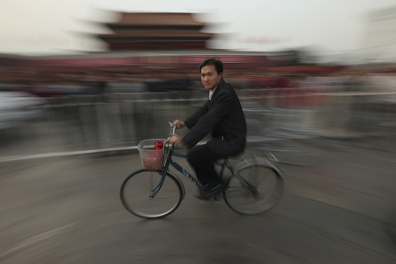 A man cycles past the entrance to the Forbidden City in Tienanmen square after a week long celebration of the 60th anniversary of communist China.