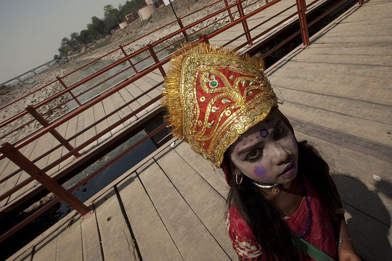 A girl in dressed as one of the gods begging on one of the bridges over the Ganges in Haridwar. 16 million pilgrims visited the 2010 Kumbh Mela festival in north India's Haridwar.