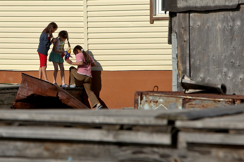 Three girls playing in a backyard in Yar-Sale. Similarly to [tag yakutsk Yakutsk], all towns built on permafrost have pipelines carrying waste, water and fuel built above the frozen ground leaving a network of bridges for children to play on.