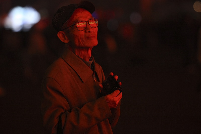 A man watches a screen in Tienanmen Square after the 60th anniversary celebrations of communist China.