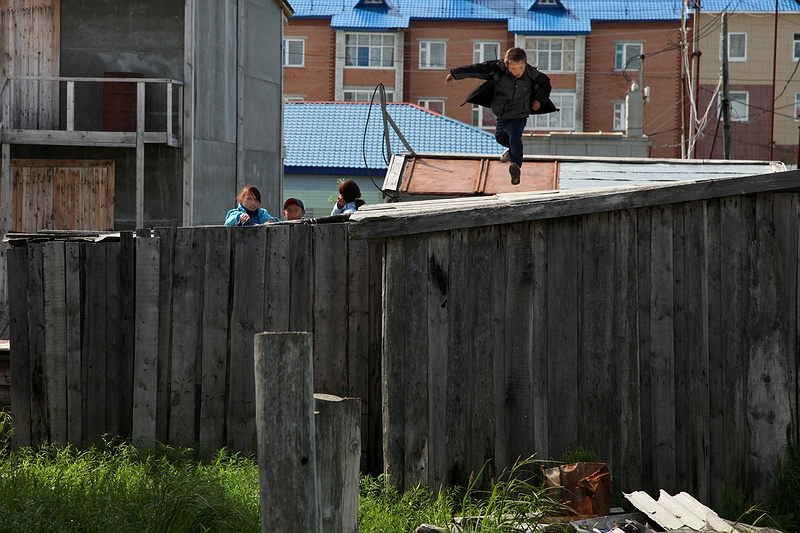 A boy jumps between garage roofs. Similarly to [tag yakutsk Yakutsk], all towns built on permafrost have pipelines carrying waste, water and fuel built above the frozen ground leaving a network of bridges for children to play on.