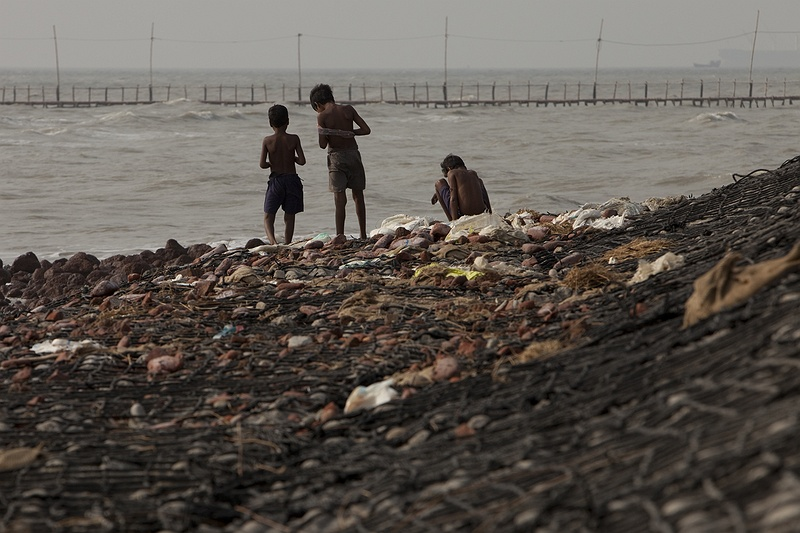 Children play on the destroyed sea defence wall by the sea front on Sagar Island. The local community prepare for the coming monsoon season by rebuilding the destroyed sea defence wall to protect themselves from increasing tidal surges and cyclones. Hundreds of people were killed and more than 22,000 homes were ravaged when cyclone Aila struck the Bay of Bengal in May 2009. If the sea continues to rise these low lying island will be destroyed and the people of Sagar Island forced from their, culture, home and livelihoods.