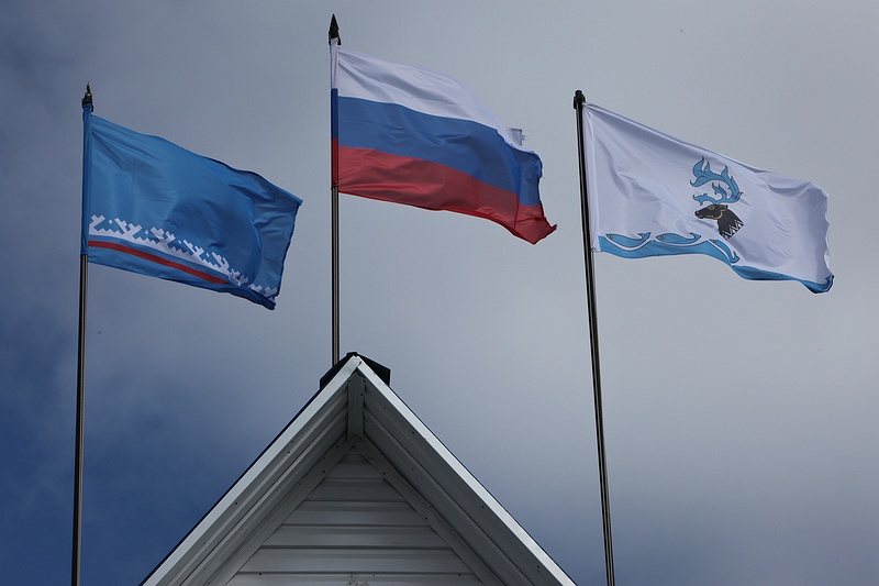 The flag of Yamal-Nenets Autonomous District sways in the breeze above the meat processing factory in Yar-Sale. The Russian flag is central and to the right another one for the reindeer community.