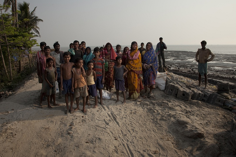 Local people involved in rebuilding the destroyed sea defence wall stand by Hooghly river, where the Ganges meet the sea. People of all ages are involved in the reconstruction of the sea defence wall by the Light house on Sagar Island. Most families have no choice but to bring their children with them to work.