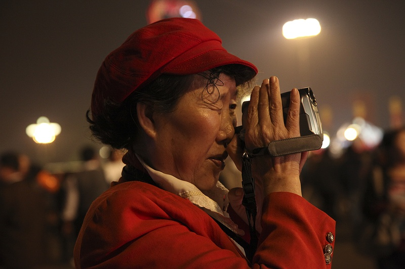 A Chinese woman films the 60th anniversary of communist China in Tienanmen Square.