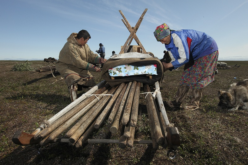 Packing up and preparing to move, Yasha and Valya strap down the kitchen table onto one of their sledges carrying the wooden pole inner structure of their home.