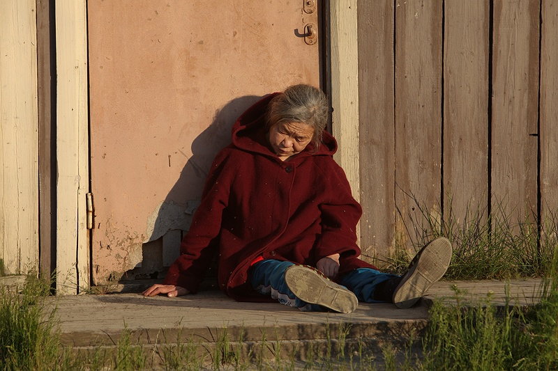 A woman outside a building in Yar-Sale. Some Nenet families have a base home in Yar-Sale where elder or studying children live while the rest of the family are out on the tundra with the reindeer. The contrast from Nenets culture to life in the town is too much for some.