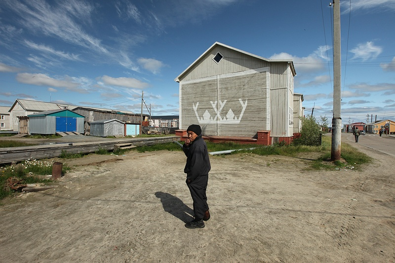 A man stands in the middle of a street in Yar-Sale. Many of the houses here have reindeer adornments. Reindeer mean everything to the Nenets culture and it is here in Yar-Sale where that culture meets the town. Children from the tribes come attend school here and it is a main stop on the reindeer migration route for the larger brigades.