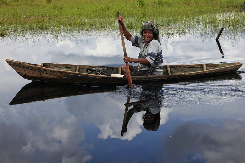 A woman from a fishing community living along the Serkap river in Riau paddles by in a traditional hand-crafted dug out canoe. These people are heavily affected by  deforestation as large quantities of nutrients  drained from the land  after logging acidify rivers, lakes and water ways. Since 1998 their catch has dropped by 70 percent reflecting the scale of the surrounding destruction.